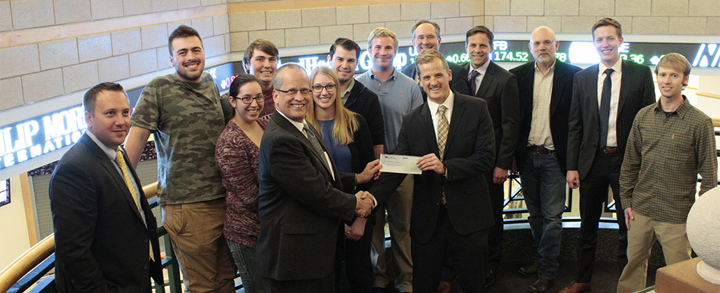 Representatives from D.A. Davidson visited the School of Business to congratulate students and faculty on earning the Fred Dickson Memorial Award; foreground, D.A. Davidson's Brad Cederberg presents a check to Business Dean Chris Shook.