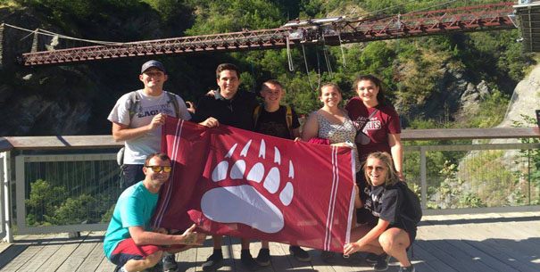 Photo of students holding Griz paw flag in New Zealand